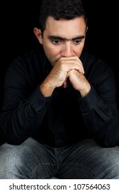 Stressed hispanic man with a sad expression isolated on black