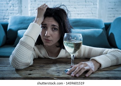 Stressed and hopeless young woman drinking a glass of wine alone at home. Feeling depressed, frustrated and weak, trying to feel better drinking. Unhealthy behavior, depression and alcoholism concept.
