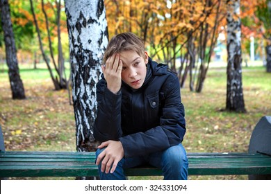 Stressed Kid sit on the Bench in the Autumn Park