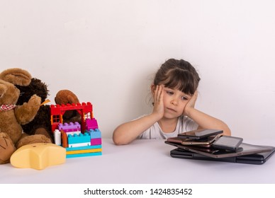 Stressed little girl sitting near phones, smartphones, laptops, pc tablets and toys. Concept of information overload. Kid under pressure overwhelmed by information