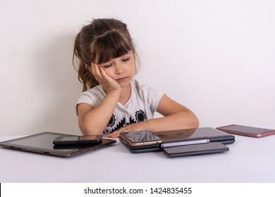 Stressed little girl sitting near phones, smartphones, laptops, pc tablets. Concept of information overload. Kid under pressure overwhelmed by information