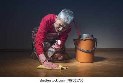 Stressed and lonely old cleaning lady in pain while working