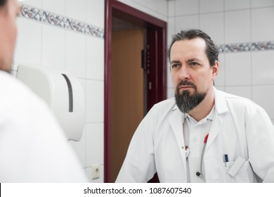 stressed looking doctor in front of an mirror is watching himself