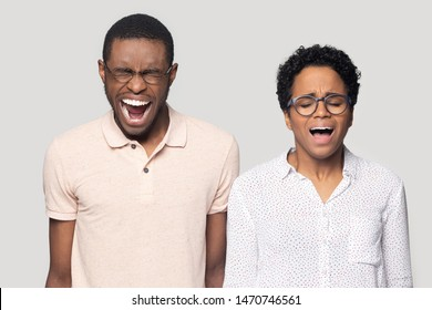 Stressed mad millennial ethnic family couple in eyewear feeling angry, screaming, shouting, yelling with widely opened mouths and closed eyes, isolated in grey studio background, conflict concept.