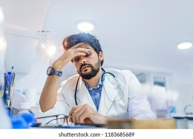 Stressed male doctor sat at his desk. Mid adult male doctor working long hours. Overworked doctor in his office. Not even doctors are exempt from burnout .