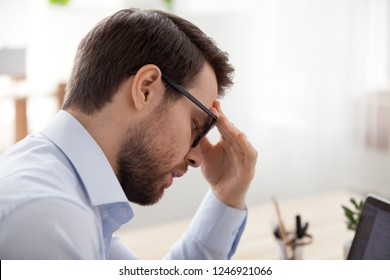 Stressed male employee sit with eyes closed suffering from headache or dizziness, ill man feel unwell have blurry vision, experience sudden eye spasm or strain at workplace. Health problem concept
