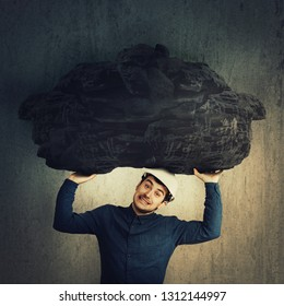 Stressed male engineer holding a huge heavy stone above head. Metaphor for the individual's persistent struggle against the challenges of life. Man making effort to carry a big rock, concept of burden