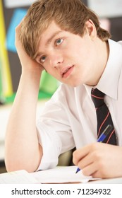 Stressed Male Teenage Student Studying In Classroom