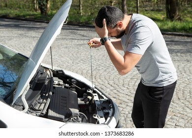 Stressed man with broken car looking at failed engine, trying to fix it