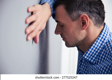 Stressed man with closed eyes leaning on the gray wall