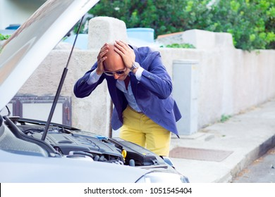 Stressed man having trouble with his broken car looking in frustration at failed engine; hands on head looking inside to the open capote top of the car. Negativehuman emotion reaction body language