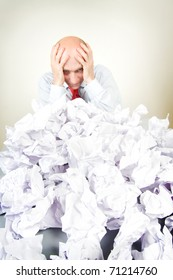 A stressed man holding his head behind a pile of papers.