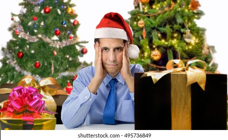 Stressed man shopping for gifts of christmas with red santa hat looking angry and distressed