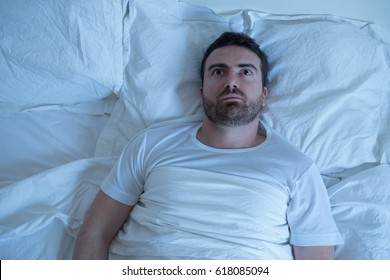 Stressed man trying to sleep in his bed at night