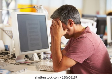 Stressed Man Working At Desk In Busy Creative Office
