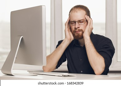 Stressed Man Working At Desk In Busy
