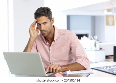 Stressed Man Working At Laptop In Home Office