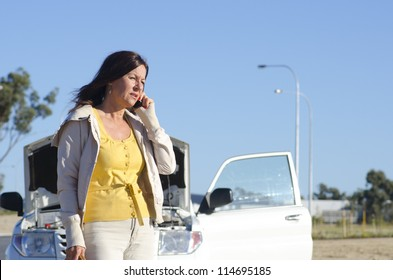Stressed mature woman breakdown with car on remote road calling for service, assistance, for help on mobile phone, isolated with blue sky as background and copy space.