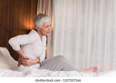 Stressed mature woman touching her painful back and feeling discomfort in her bedroom, Back pain concept