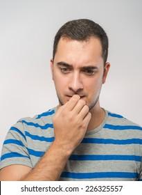 stressed mid adult businessman biting fingernails