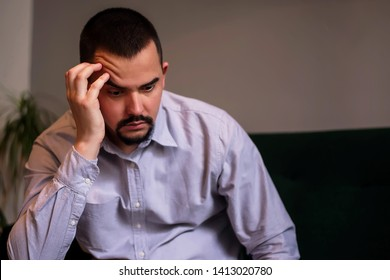 Stressed middle-aged man in wrinkled gray shirt sitting indoor with raised eyebrow having put head on hand. Thoughts, depression, problems concept. Midlife crisis. Room for copy text