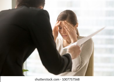 Stressed millennial woman listening claims of angry boss on mistakes in report. Frightened by prospect of dismissal female office worker worried because of serious fail in work. Scandalous, mad client