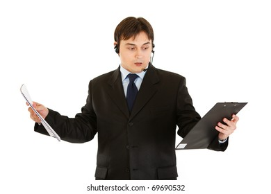 Stressed modern businessman with headset holding documents in hands isolated on white