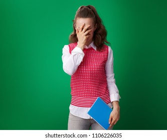 stressed modern student woman in a red waistcoat with a blue notebook facepalm isolated on green