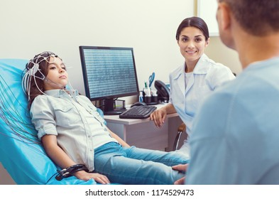 Stressed moment. Smiling female doctor smiling to a father while his poor little girl getting her brain analyzed by an electroencephalograph.