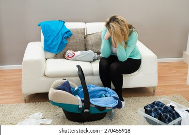 Stressed Mother With The Baby Sitting On Sofa