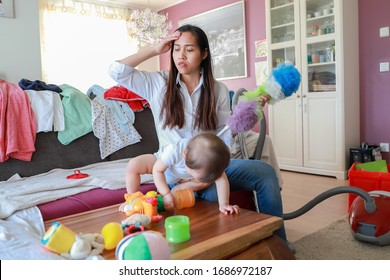 Stressed mother working from home with messy room and her little baby playing with many toys. Asian housewife tired and suffering from headache overwork.
