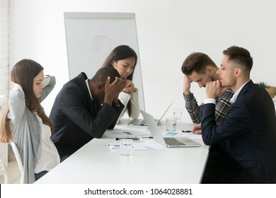 Stressed multiracial team thinking of problem solution at emergency office meeting, sad diverse business people group shocked by bad news, upset colleagues in panic after company bankruptcy concept