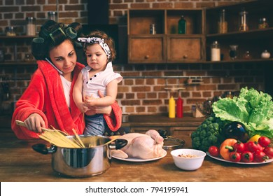 Stressed mum at home. Young mother with little child in the home kitchen. Woman doing many tasks while looks after her baby