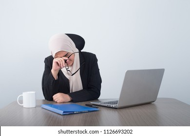 Stressed Muslim business woman take the glasses off her face crying getting tired of work, sitting on her desk, opened laptop on the front of her.