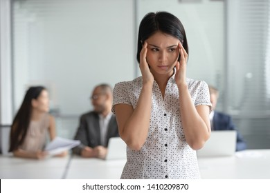 Stressed nervous asian business woman employee feel headache at work, frustrated tired anxious japanese female executive suffer from migraine overwork dizziness at workplace massage temples in office