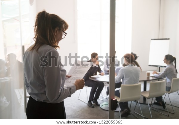 Stressed nervous stuttering inexperienced businesswoman standing at office door feeling afraid worried before performance reading paper preparing business speech, public speaking fear anxiety concept
