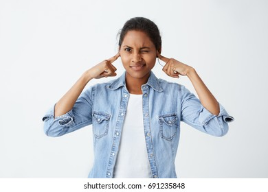 Stressed nervous young dark-skinned woman with black hair closing eyes and plugging ears with fingers, annoyed with loud sound or music coming from neighbour's flat. Stop making this noise