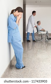 Stressed nurse leaning against wall with doctor pushing patient in wheelchair
