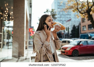 Stressed office woman eating on the way and talking on the phone outside