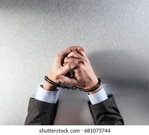 stressed out businessman hands bothered with handcuffs suffering at custody for concept of suspicious business, hostage or corporate justice, above view