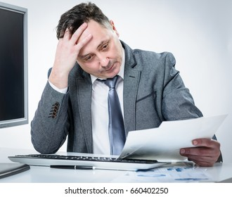 Stressed out businessman working on documents