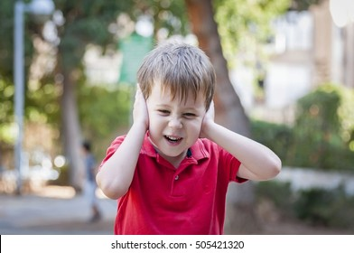Stressed out little 5-year old Caucasian little boy outside closing his ears and screaming of pain, trauma, traumatic experience and loud noise stock image. Autism, autistic child, asperger syndrome