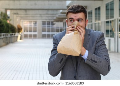 Stressed out man breathing through paper bag
