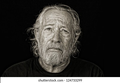 Stressed out older man isolated against black sepia toned