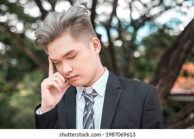 An stressed out and tired young asian man with dyed ash blonde hair. Overworked Gen Z worker.