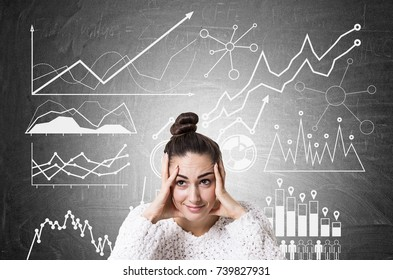 Stressed out young woman wearing a white sweater and holding her head with both hands. Blackboard background with graphs on it