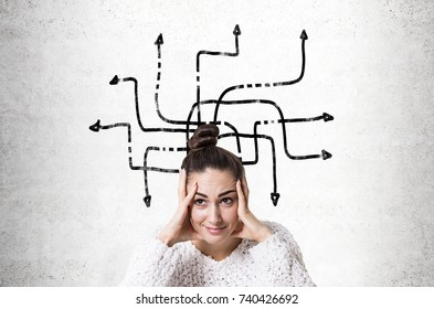 Stressed out young woman wearing a white sweater and holding her head with both hands. Concrete wall background with an arrow labyrinth.