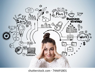 Stressed out young woman wearing a white sweater and holding her head with both hands near a gray wall with a business plan sketch drawn on it