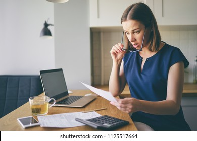 Stressed over bills. Portrait of surprised young woman using a laptop computer sitting at her kitchen holding utility bill and bank statements. Home interior.