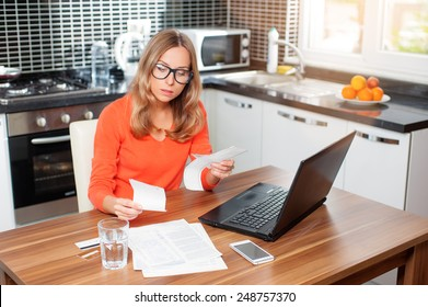 stressed over bills. portrait of a young  woman using a laptop computer sitting at her kitchen holding utility bills and bank statements being thoughtful and worried. Home kitchen interior